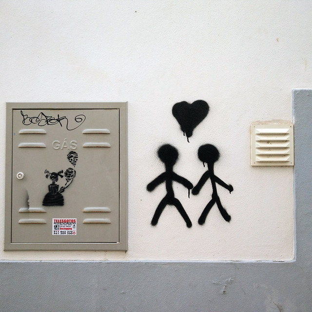 Ada Wanders/Włóczykijada. Street Art in Lagos. Sticky figures with heart and a girl with gas masks.