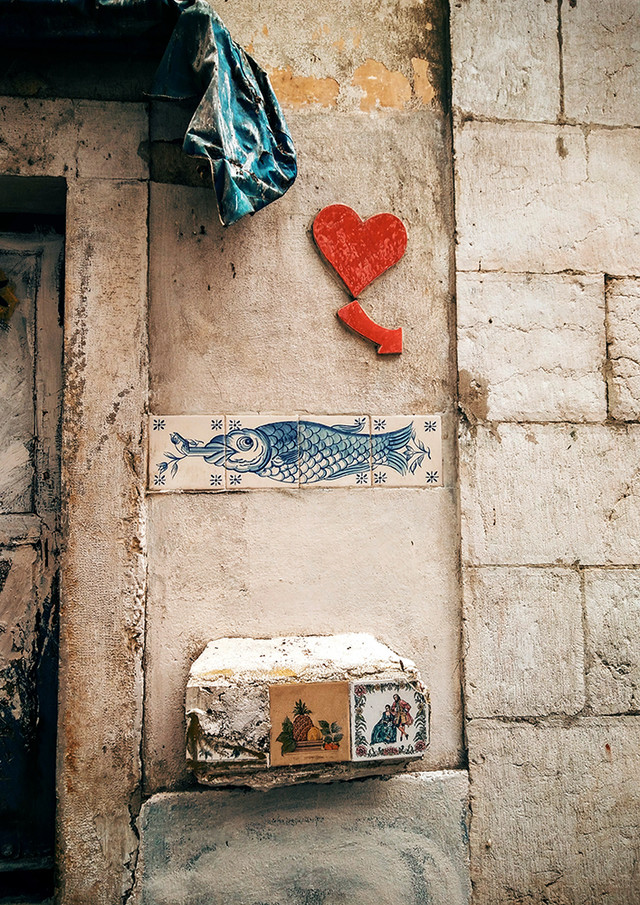 Ada Wanders/Włóczykijada. Red heart with an arrow, fish on azulejos and tiles with pictures of people and fruit in Alfama in Lisbon.