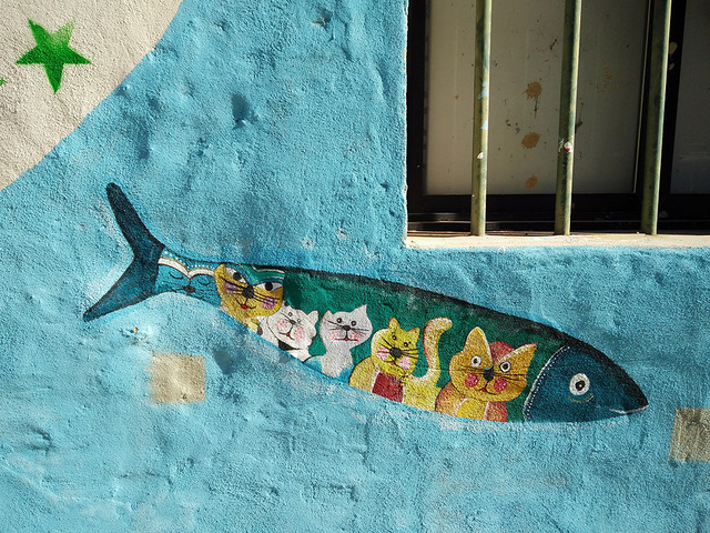 Ada Wanders/Włóczykijada. Street Art: Picture of fish with cats inside in Portimão